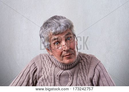 Senior elderly man in glasses looking with wide open eyes having clever expression. A wise grandfather in glasses having surprised expression isolated over white background. People and emotions