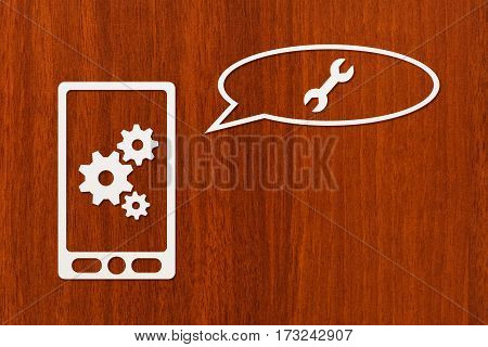 Paper tablet or smartphone with cogwheels wrench and speech bubble dark wooden background. Abstract conceptual image