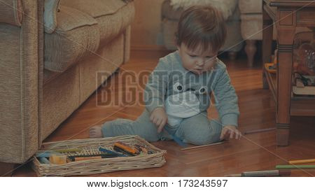 Little baby playing on the floor with a plastic knife. Eye level shot