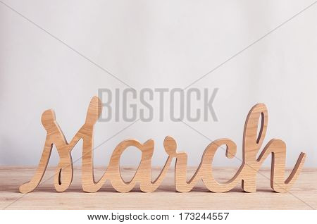 March - word carved out of wood. Spring time concept.