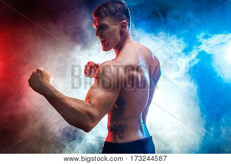 Studio portrait of fighting muscular man in smoke