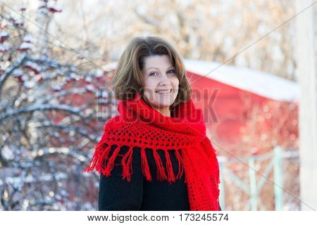 Russian woman stands on a background of the house and viburnum
