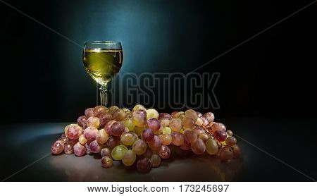 on shiny reflecting background is a big bunch of ripe grapes and is transparent glass of white wine