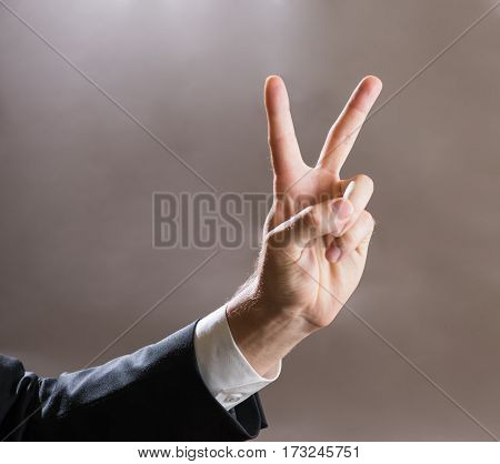 businessman showing V shape fingers represent his victory, success.