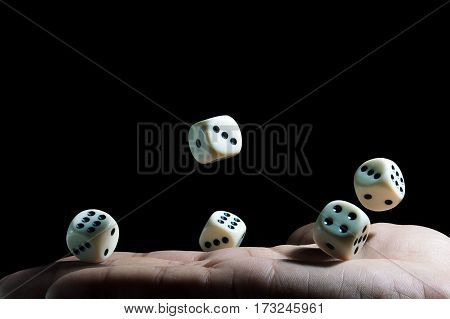drop of dice on the hand on black background