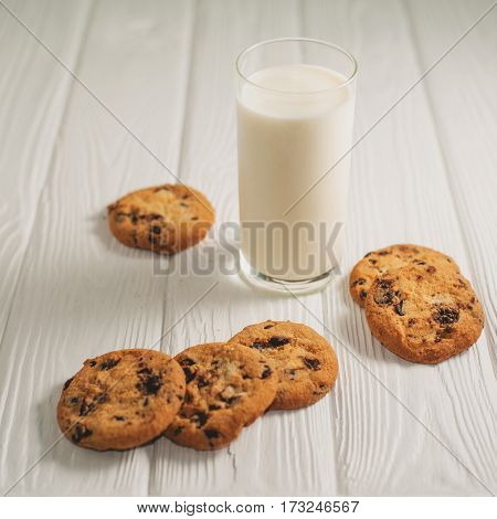glass of milk and cookies with chocolate on a white wooden background