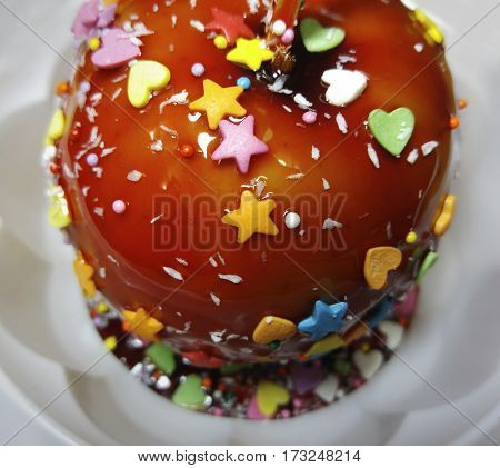 Apple in a caramel glaze. Strew of hearts stars balls. Apple close-up in white plate. Food.