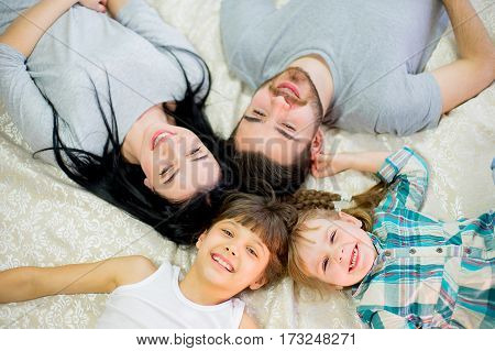 young family with children posing on the bed in the hotel