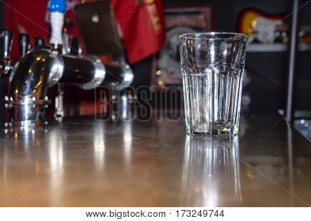 The empty glass is on the bar