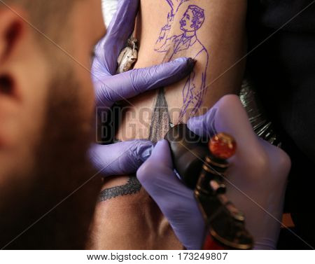 Professional artist making tattoo in salon, close up view