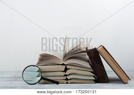 Open book hardback colorful books on wooden table. Magnifier. Back to school. Copy space for text. Education business concept