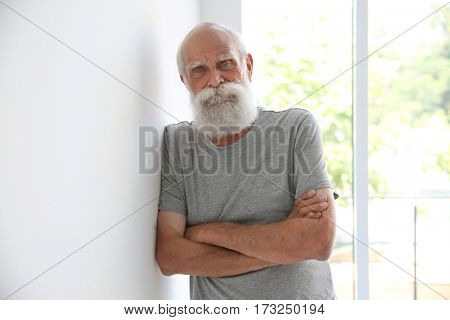 Old man standing beside window