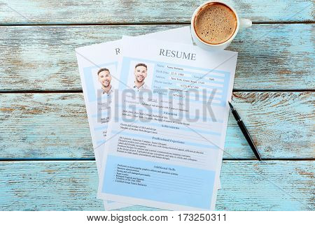 Cup of coffee and completed resume forms on wooden background