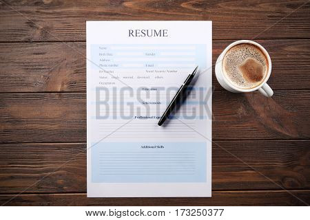Cup of coffee and resume form on wooden background