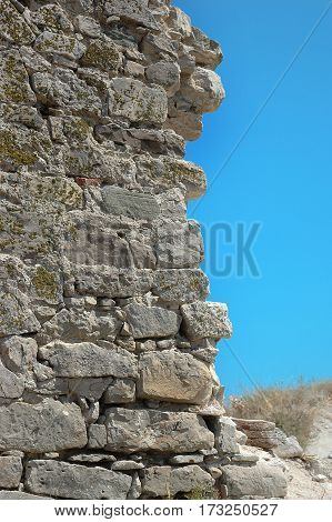collapsed stone wall in ruins on sky background