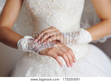 bride in white dress puts gloves on hands.