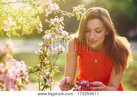 beautiful young woman smelling a flower in the spring park.