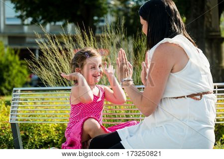 Mother playing with her adorable daughter on a sunny summer day