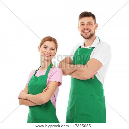 Young man and woman in green aprons isolated on white background