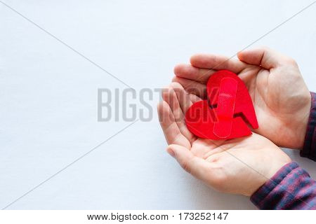 Man Holding Broken Heart With A Patch On A White Background
