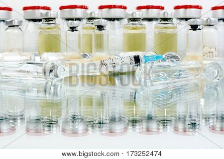 Glass vials of vaccine. Medications for injection and reflection in the glass