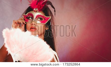 Holidays people and celebration concept. African woman with carnival venetian masks holding feather fan in hand over festive background.