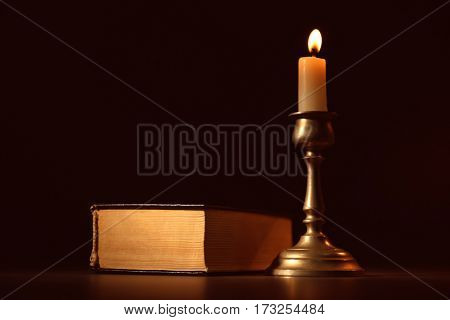 Bible and burning candle on dark background
