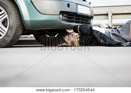 Auto assistance and insurance troubles while traveling concept. Woman trying to repair her broken car checking what is under automobile.
