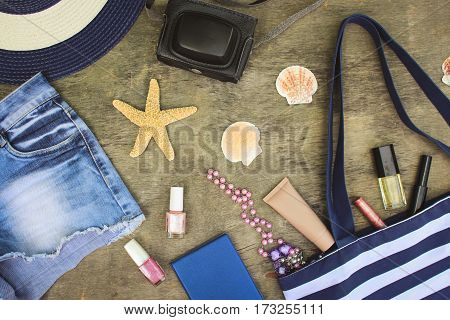Beach bag, sun hat, cosmetics, denim shorts, camera, seashells on old wooden background. Top view. Toned image.