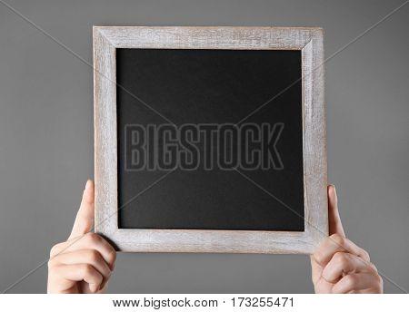 Female hands holding empty blackboard on color background
