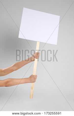 Male hands holding blank banner on wooden stick against light background
