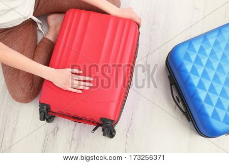 Young woman packing suitcases on floor at home