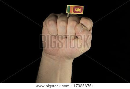 Man Hand Fist With Sri Lankan Flag Isolated On Black Background