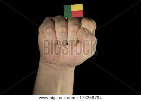 Man Hand Fist With Benin Flag Isolated On Black Background