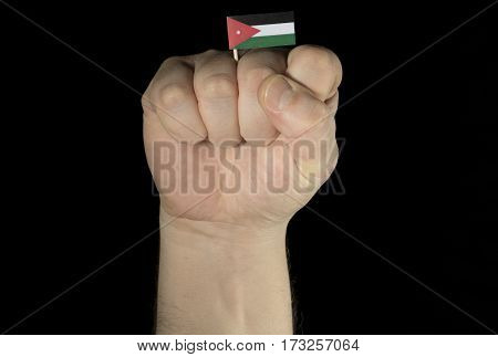 Man Hand Fist With Jordanian Flag Isolated On Black Background