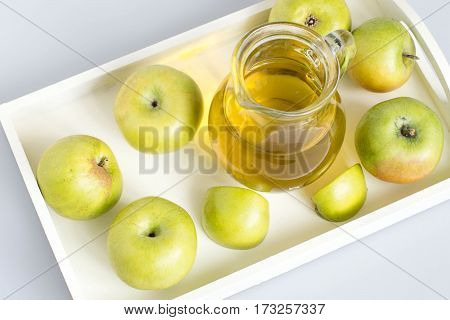 Source of natural vitamins. Small green apples and a glass jug with fresh apple juice on a white tray on a light background.