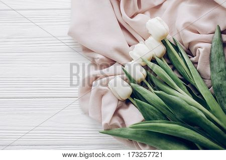 stylish white tulips on beige soft fabric and rustic wooden table background top view. hello spring flat lay. soft light tenderness atmospheric moment. space for text. modern image