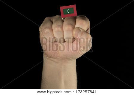 Man Hand Fist With Maldivian Flag Isolated On Black Background