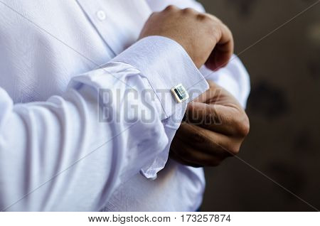 The handsome groom wears a wedding cufflinks. Wedding preparation