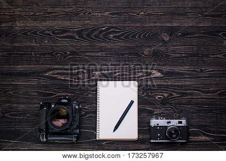 Old retro cameramodern digital camera and notebook with pen on dark wooden table