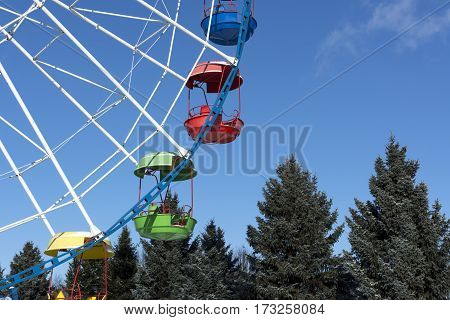 Ferris wheel with colored cabins on the blue sky background Sunny day trees spruce