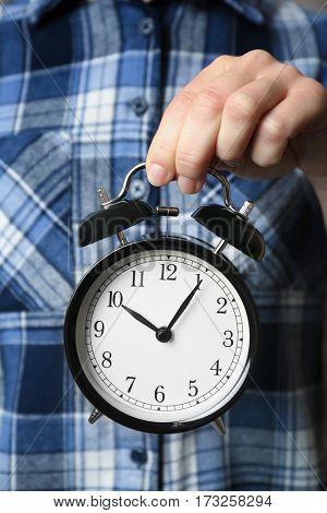 Woman holding vintage alarm clock