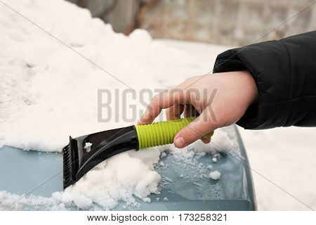 Man removing snow from car with snow scraper