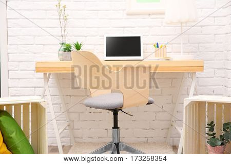 Workplace with laptop on desk in modern room