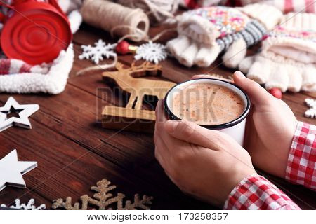 Male hands with cup of cocoa and Christmas decorations on wooden background