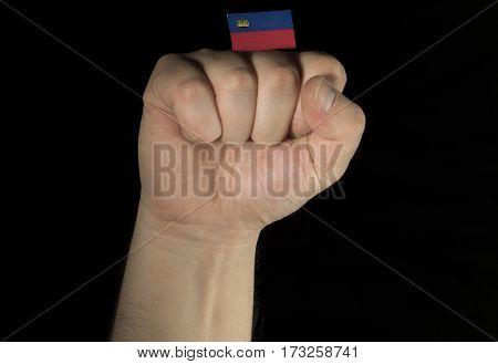 Man Hand Fist With Liechtenstein Flag Isolated On Black Background