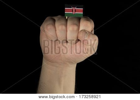 Man Hand Fist With Kenyan Flag Isolated On Black Background