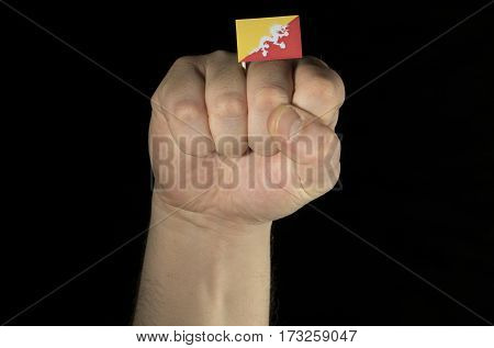 Man Hand Fist With Bhutanese Flag Isolated On Black Background