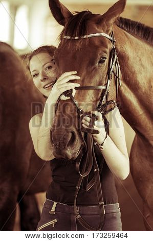 Woman Hugging Brown Horse In Stable