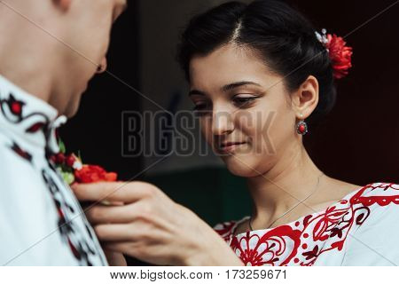 Gorgeous Brunette Bride Putting On Boutonniere On The Groom